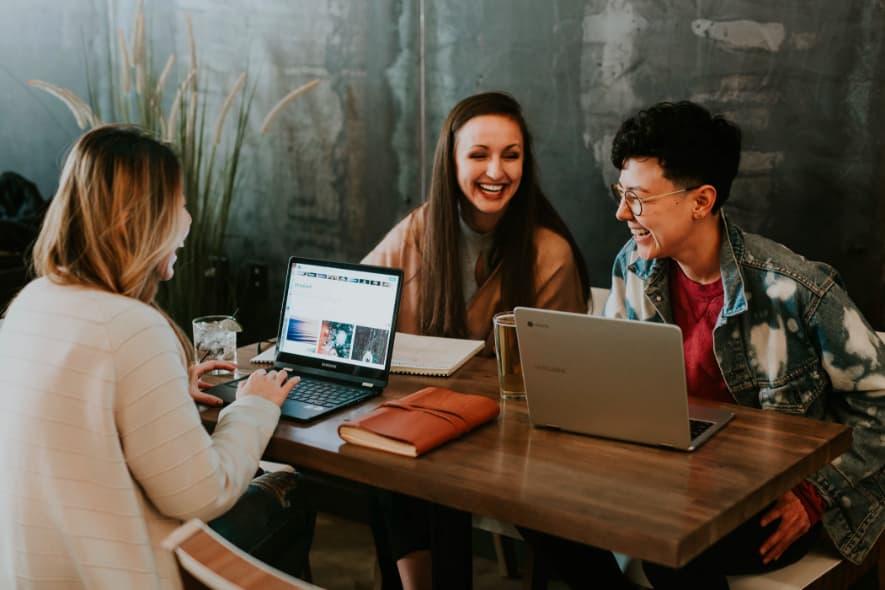 grafika dekoracyjna - przedstawiająca trójkę znajomych pracujących iśmiejących się przy laptopach