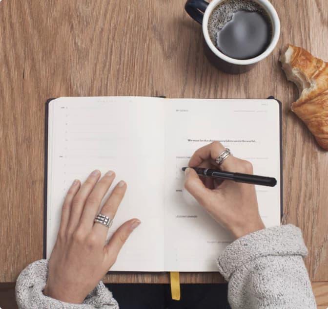 grafika dekoracyjna - przedstawiająca notes, ręce i kawę
